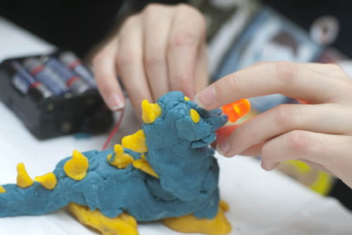 Image: Squishy Circuits. Model dinosaur made using conductive play dough. LED light in nose is lit up. Taken at The Academy of Natural Sciences of Drexel University