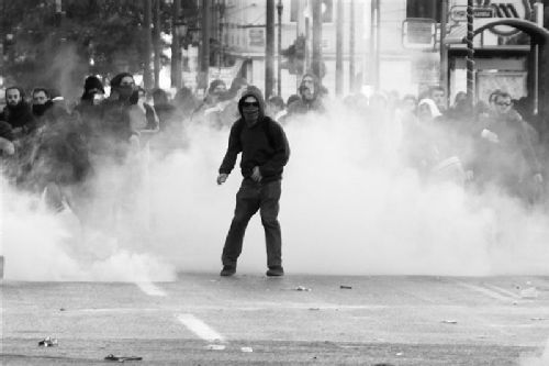 Image. Greek riots - protester stands in front of cloud of smoke.